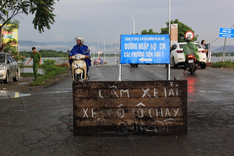 Tuyến tỉnh lộ 421B qua bị cắt đứt do nước ngập quá sâu. Lực lượng chức năng phải đặt biển cảnh báo các phương tiện qua đoạn đường ngập (Ảnh: Trần Thanh)