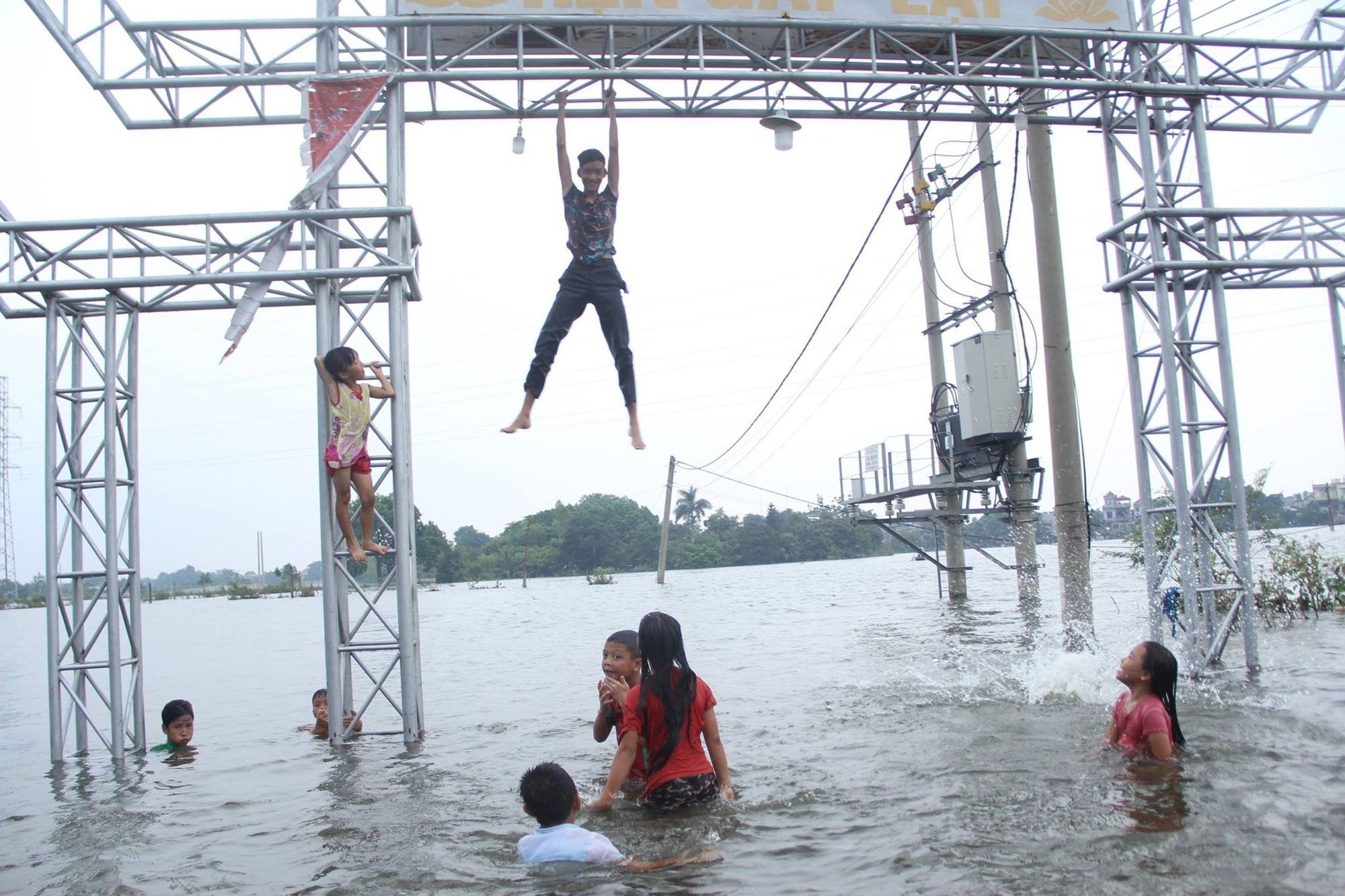 Đám trẻ đùa nghịch giữa vùng nước lụt bất chấp nguy hiểm.