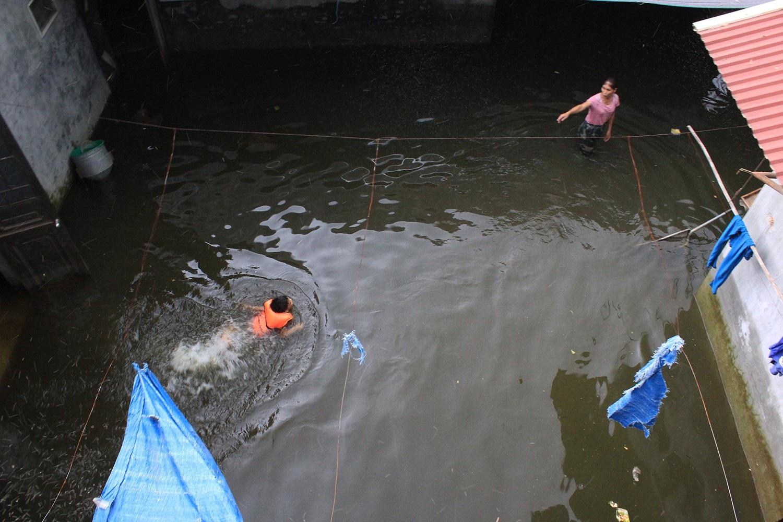 Con trai vợ chồng anh Ngọc thoả thích bơi nghịch ngay trong sân nhà, trong làn nước đen bẩn, mất vệ sinh (Ảnh: Trần Thanh)