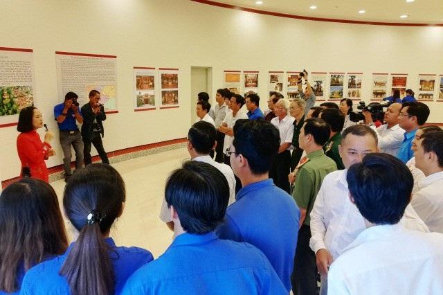 Các đại biểu, người dân nghe thuyết minh về các tư liệu tại triển lãm.