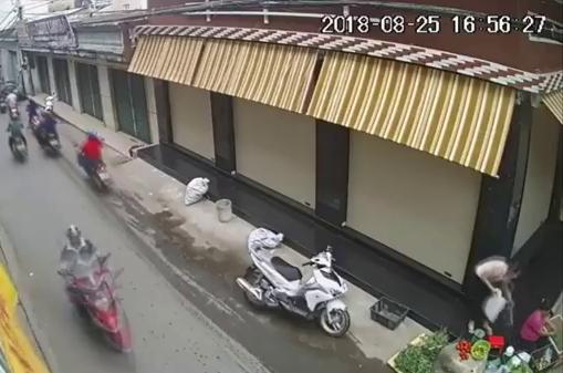 Bà Liễu lấy trộm giỏ sách khi bà chủ sạp rau đang bán hàng (hình cắt từ clip)