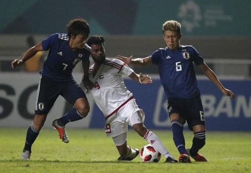 Hai cầu thủ Nhật Bản, Hara (trái) và Hatsuse (phải) vây Musabbah (giữa) của UAE