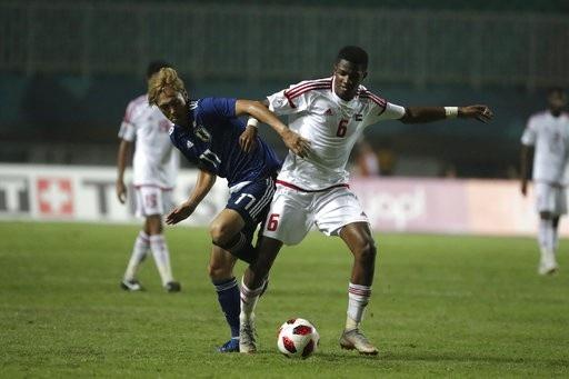 Salim (phải, UAE) tranh bóng với Kamiya (trái, Nhật Bản)