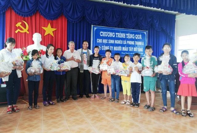 Ông Nguyễn Kiên Nhẫn- Chủ tịch Hội Khuyến học tỉnh Bạc Liêu và ông Nguyễn Phú- Giám đốc Công ty Người mẫu Tây Đô trao quà đến các em học sinh nghèo.