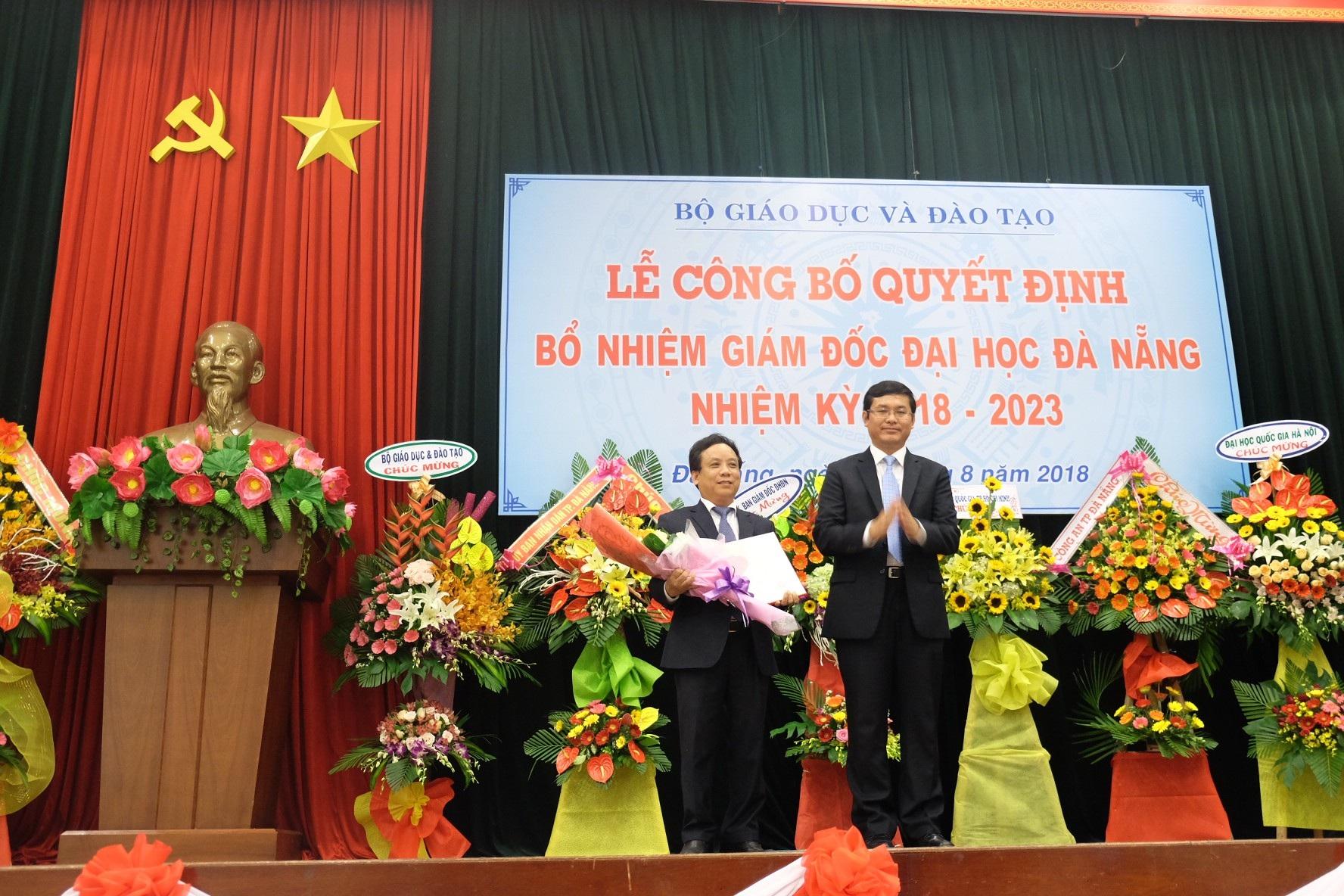 PGS.TS Nguyễn Ngọc Vũ (bên trái) nhận Quyết định của Bộ GD-ĐT về việc bổ nhiệm Giám đốc ĐH Đà Nẵng nhiệm kỳ 2018 - 2023