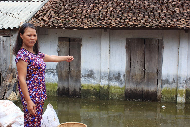 Bà Mừng chỉ vào phía nhà kho của gia đình, nơi mà cách đây chỉ vài ngày nước ngập đến gần mái ngói (Ảnh: Trần Thanh)