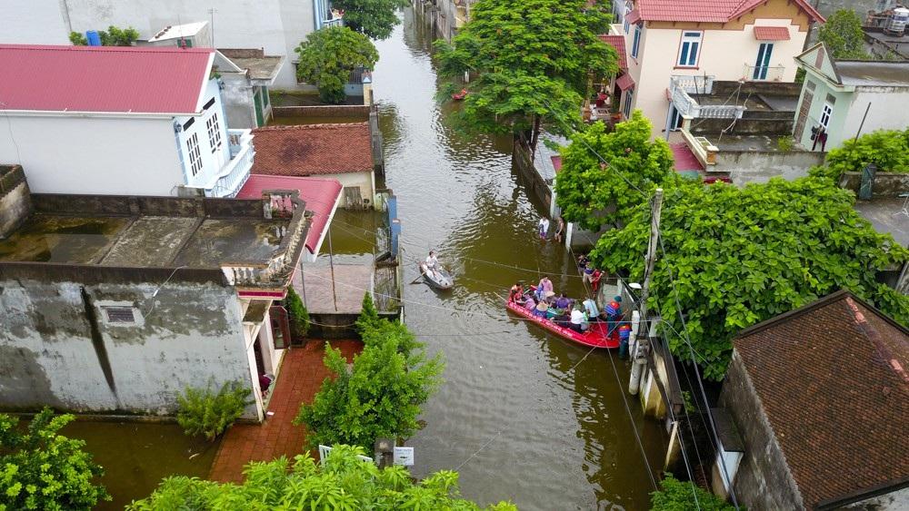 Cảnh nước ngập khắp xóm, người dân phải dùng thuyền để đi lại.