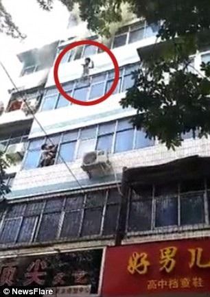Một đứa trẻ được mẹ ném từ cửa sổ tầng 4 khi xảy ra hỏa hoạn (Ảnh: Newsflare)