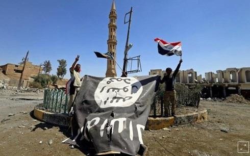 Lực lượng quân sự Shiite thu cờ đen của IS trong một trận đánh với quân IS ở Tal Afar, Iraq, hồi tháng 8/2017. Ảnh: Reuters.