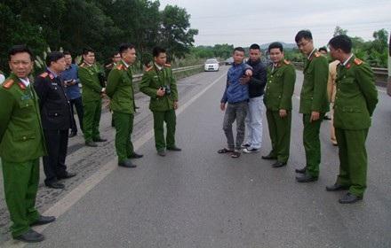 Hoàng Văn Trường (áo xanh) được dẫn giải đến hiện trường để phục vụ quá trình điều tra (Ảnh: Hồng Ngân).