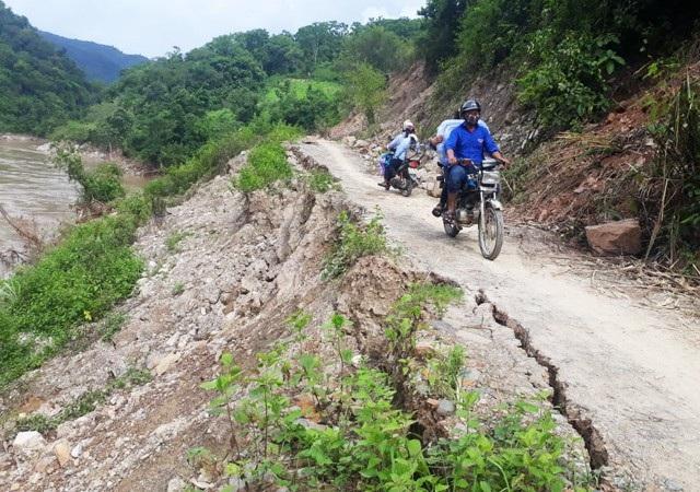 Người dân di chuyển chênh vênh trên con đường đang bị sông bóc đến tim đường