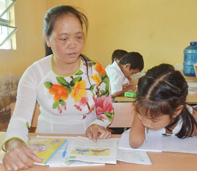 Cô Thúy đang hướng dẫn em Thảo học, viết bài.