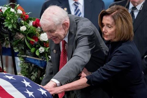 Buổi lễ có sự xuất hiện của nghị sĩ đảng Cộng hòa Sam Johnson, người bạn cùng buồng giam với ông McCain ở nhà tù Hỏa Lò, Việt Nam trong 18 tháng khi họ đều là tù nhân chiến tranh. Hình ảnh ông Johnson run rẩy bước từ xe lăn, hòa mình vào dòng người đi quanh quan tài của ông McCain đã gây xúc động mạnh. Trong ảnh: Lãnh đạo phe thiểu số tại Nghị viện Mỹ, nghị sĩ đảng Dân chủ Nancy Pelosi đã giúp ông Johnson bước đi. Hai chính trị gia xúc động chạm tay vào quan tài như một lời chào tạm biệt tới người bạn, người đồng nghiệp.