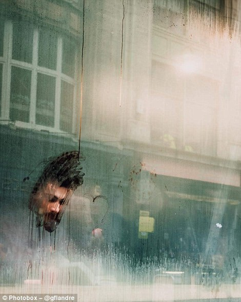 Một người đàn ông đang ngồi đọc sách phía sau cửa kính mờ hơi sương ở London