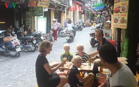 Nhiều khách du lịch quốc tế tìm đến Việt Nam vì mê phong cảnh thiên nhiên, ẩm thực, văn hóa truyền thống... (Ảnh: Khách nước ngoài thưởng thức món ăn Việt Nam tại phổ cổ Hà Nội.
