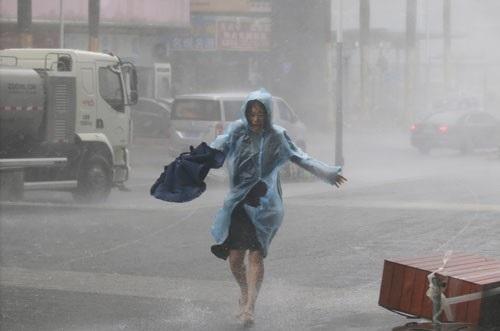 Cô gái vật lộn giữa mưa to gió lớn tại Thẩm Quyến, Trung Quốc khi bão Mangkhut tấn công Ảnh: REUTERS