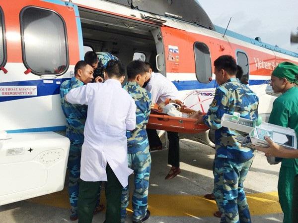 Các y, bác sĩ Bệnh viện Quân Y 175 cùng cán bộ, chiến sĩ Hải quân Phan Vinh đưa hai bệnh nhân lên máy bay về đất liền cứu chữa.