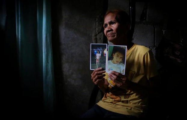 Bà Mimi Garcia cầm ảnh của con trai và con dâu - hai người bị những đối tượng lạ mặt bắn chết tại thành phố Caloocan năm 2016 (Ảnh: Raffy Lerma)