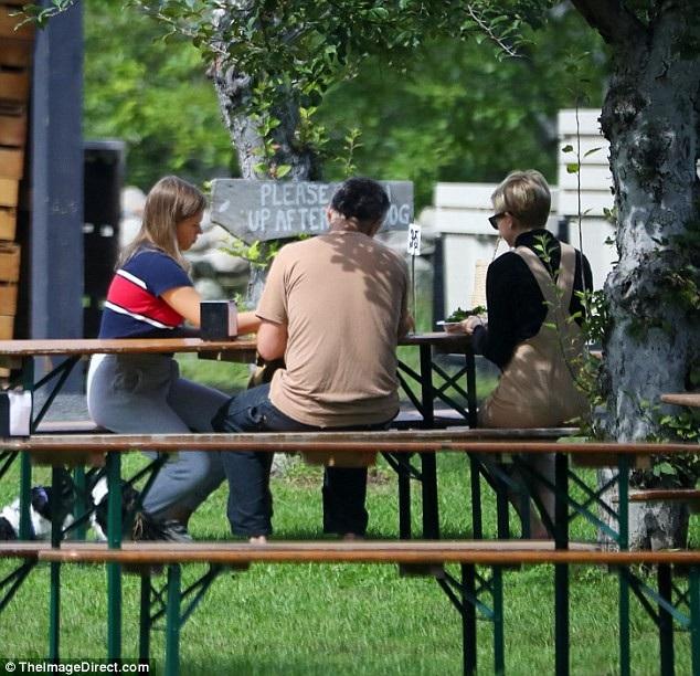 Cả gia đình ngồi ăn trưa vui vẻ trong công viên.