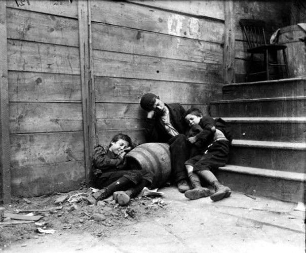 Những đứa trẻ vô gia cư ngủ gục bên một góc cầu thang ở khu Lower East Side những năm 1890./.