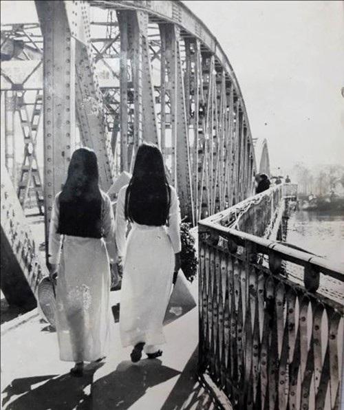 Nữ sinh Huế lãng mạn trong tà áo dài và nón lá đi học về qua cầu Trường Tiền (ảnh tư liệu)