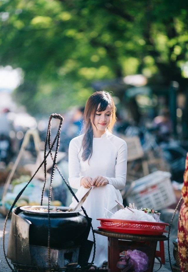 Nữ sinh vận áo dài duyên dáng bên gánh Bún bò Huế ở chợ Đông Ba (ảnh: Nguyễn Thanh Cường)