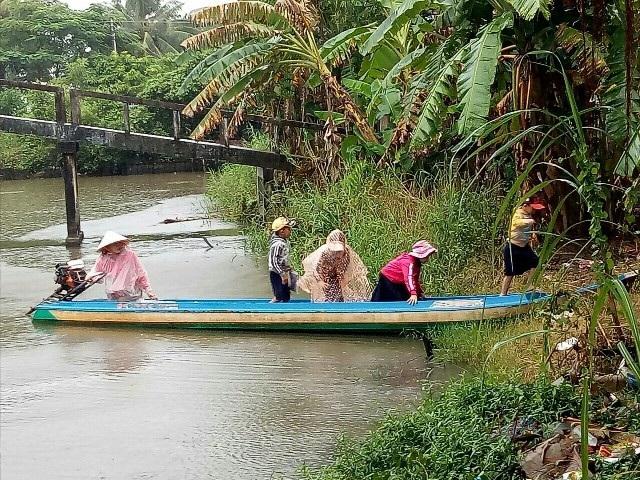 Sáng nay, trời đổ mưa, nhiều phụ huynh ở huyện U Minh (tỉnh Cà Mau) phải đội mưa đưa con em bằng xuồng máy đến dự khai giảng năm học mới.