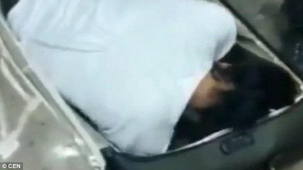 Khoảnh khắc chiếc vali được mở ra và cô gái đang nằm ẩn mình bên trong, che mặt để không ai nhìn thấy