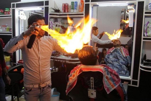 Một người thợ Pakistan cắt tóc bằng lửa cho khách hàng nam