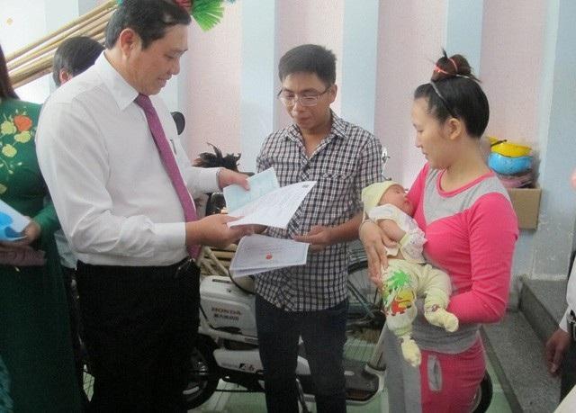 Chủ tịch UBND TP Đà Nẵng Huỳnh Đức Thơ trao giấy khai sinh, thẻ bảo hiểm y tế, hộ khẩu tại gia đình cho một trẻ ở phường Mân Thái (quận Sơn Trà)