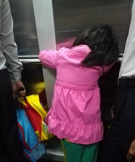 Một học sinh TPHCM tranh thủ ngủ trong thang máy khi chuẩn bị đến trường. (Ảnh: Hoài Nam)