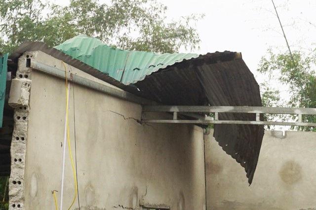 Một phần mái tôn bị hất lên, vương trên khung thép mái che của sân