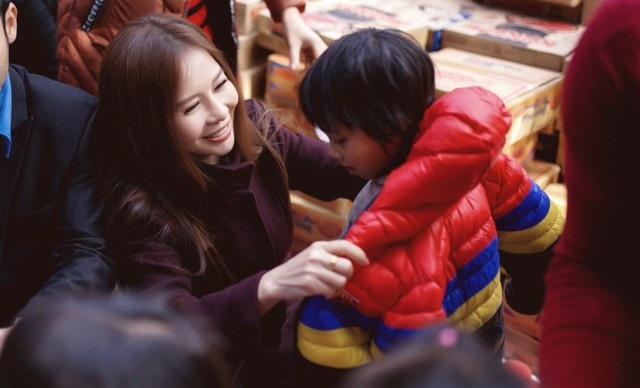 Nữ doanh nhận không giấu được niềm hạnh phúc khi tự tay mình mặc những chiếc áo ấm cho trẻ em nghèo.