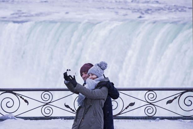 Bất chấp giá lạnh khắc nghiệt, nhiều du khách vẫn không bỏ lỡ cơ hội ghi lại những hình ảnh về hiện tượng thiên nhiên hy hữu này. (Ảnh: Getty)