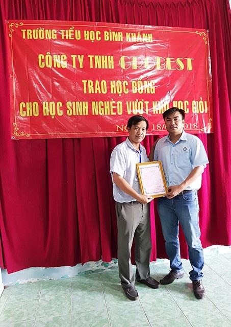 Thầy Đặng Thái Bình (bên trái) - Hiệu trưởng Trường Tiểu học Bình Khánh cảm ơn các nhà tài trợ và Báo Dân Trí