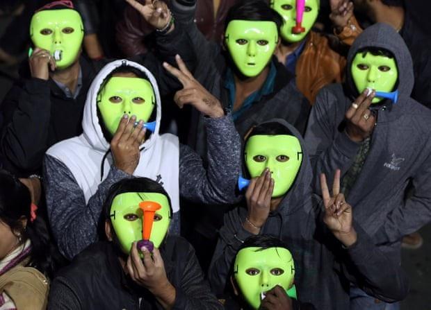 Nhiều người mang mặt nạ, thổi kèn dự sự kiện đón năm mới ở Ahmedabad, Ấn Độ. (Ảnh: Reuters)