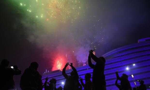 Người dân cầm điện thoại ghi lại những khoảnh khắc bắn pháo hoa trong đêm giao thừa tại Rawalpindi, Pakistan. (Ảnh: AFP)