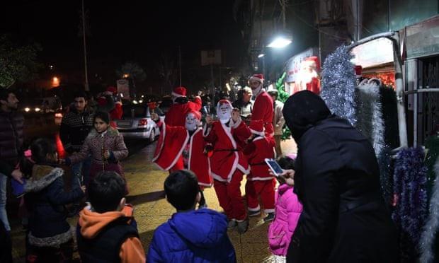 Người dân hóa trang thành ông già Noel đón năm mới tại thành phố Aleppo, Syria. (Ảnh: AFP)