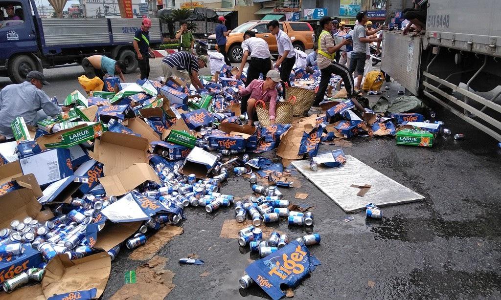 Xe tải ôm cua, hàng trăm thùng bia đổ tràn xuống đường - Ảnh 1.