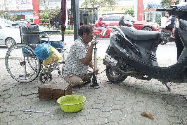 Người đàn ông cụt hai chân vẫn đi sửa xe khắp phố - Ảnh 1.