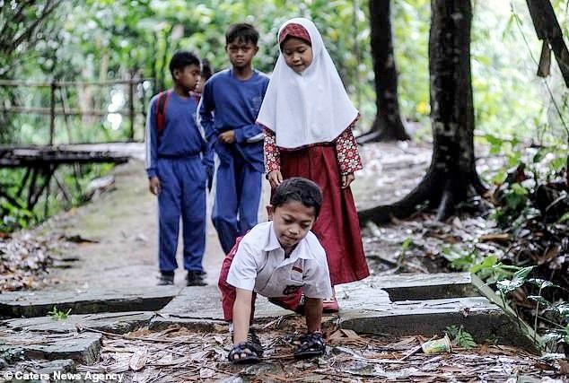 Cậu bé phải bò quãng đường 3 km mỗi ngày để tới trường.