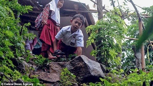 Cậu bé Adul bò tới trường qua những bậc thang dốc và những con đường gập ghềnh trong rừng.