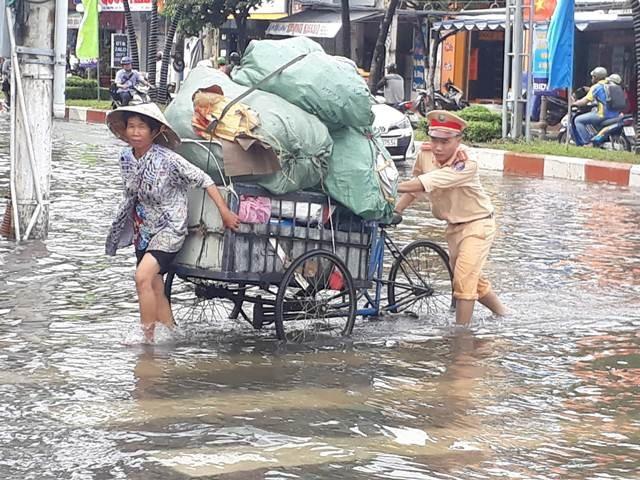 Lực lượng CSGT Bạc Liêu hỗ trợ người dân khi nước ngập.