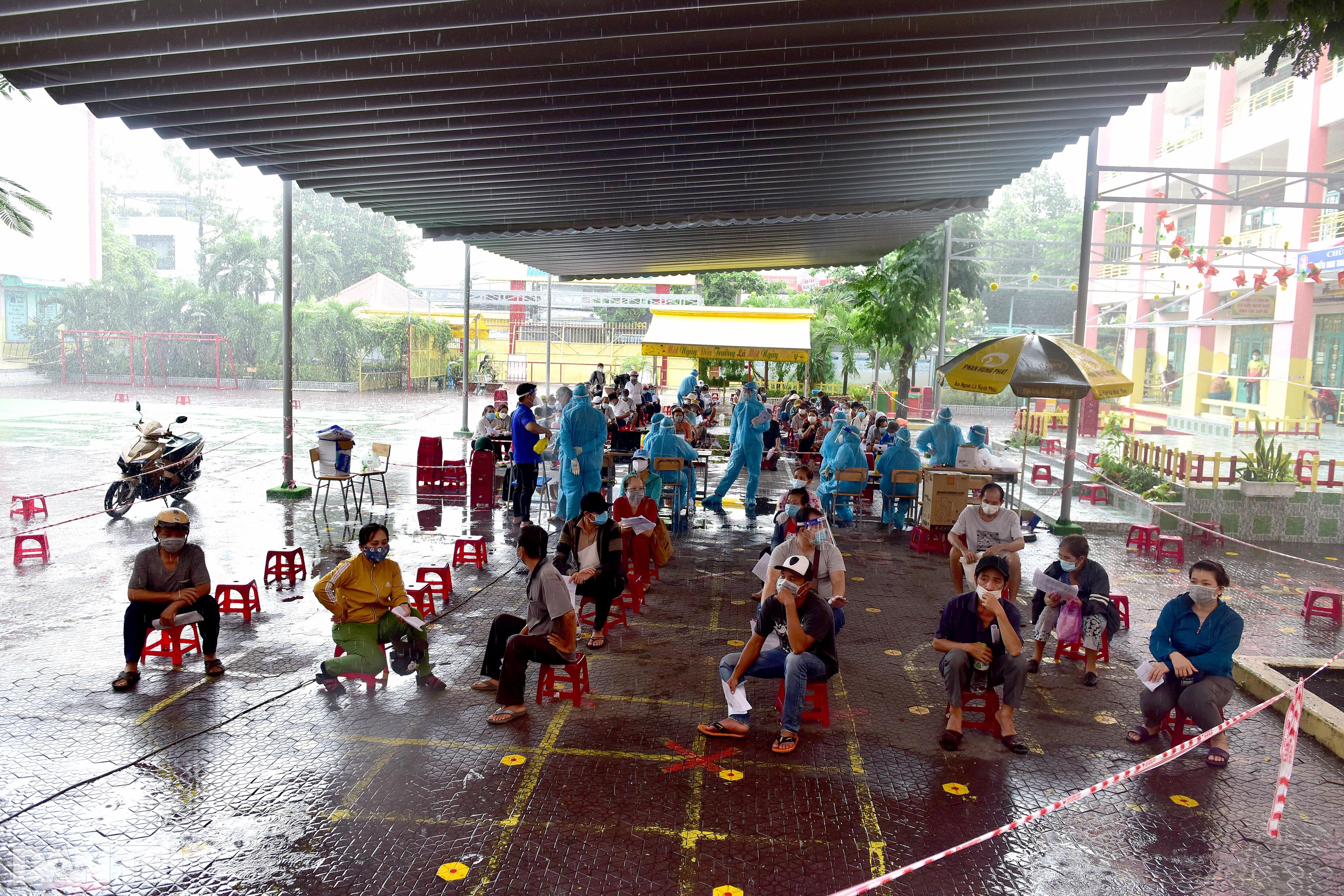 Người dân Sài Gòn xếp hàng trong mưa hơn 2 tiếng chờ tiêm vắc xin - 4