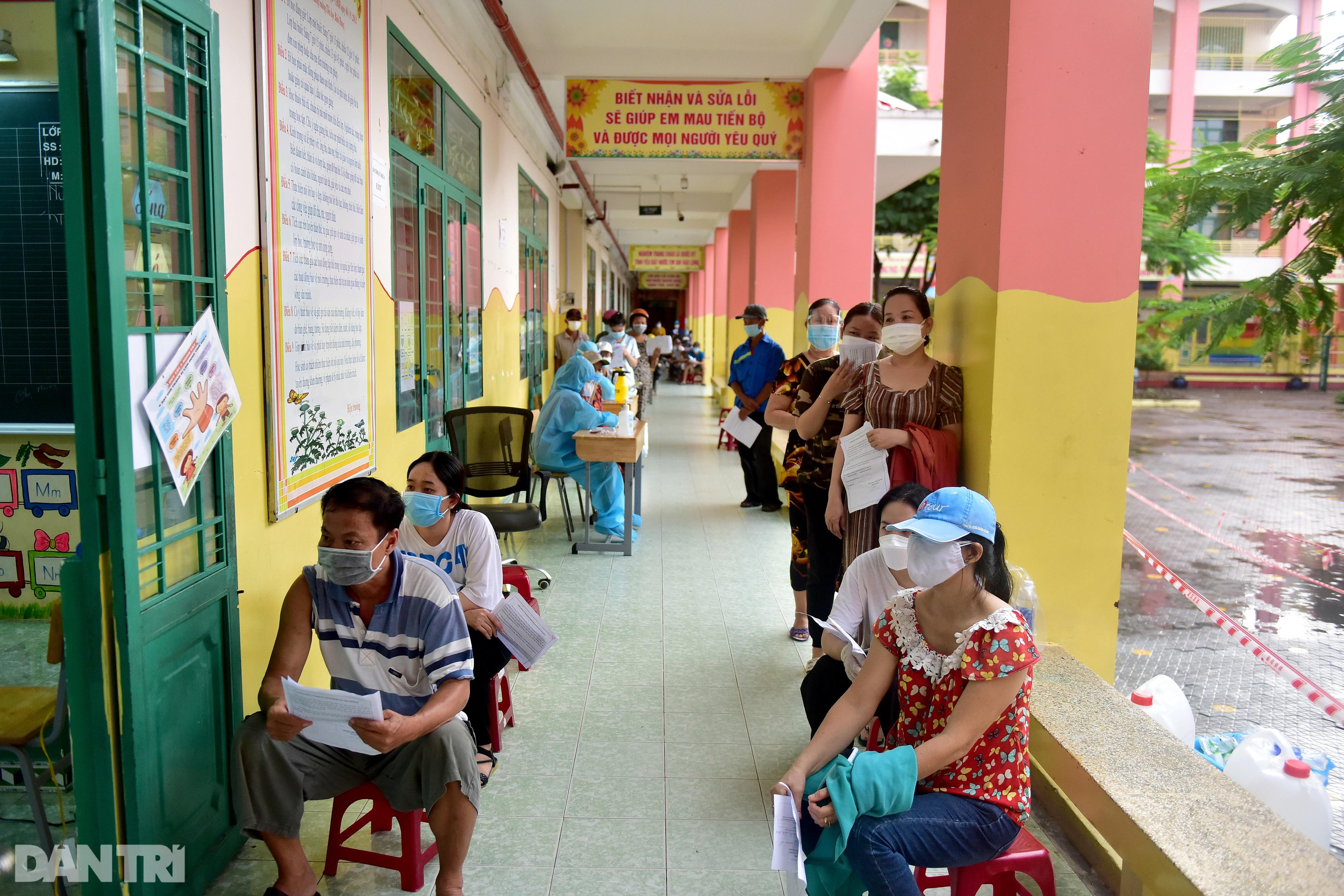 Người dân Sài Gòn xếp hàng trong mưa hơn 2 tiếng chờ tiêm vắc xin - 13