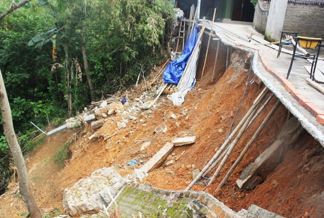 Một đoạn đường bê tông bị trôi hết đất nền, trơ lại mặt đường. Các hộ dân phải dùng cọc chống đỡ để giữ đường đi lại.