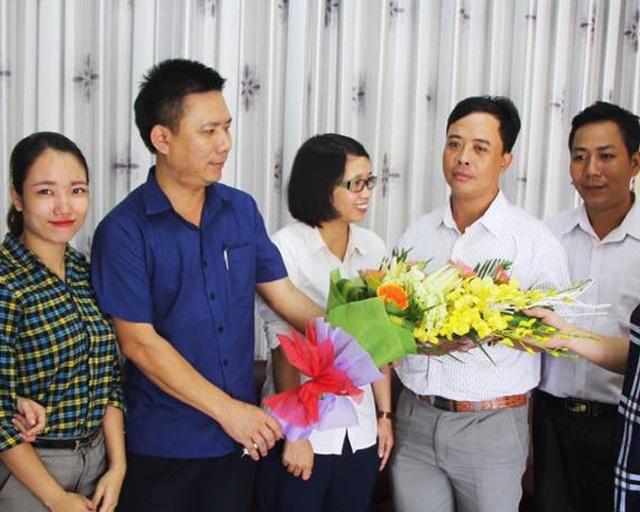 Luật sư Trọng Hải (áo xanh) tặng hoa chúc mừng anh Sửu sau khi vụ việc được giải quyết (ảnh T.Hoài).