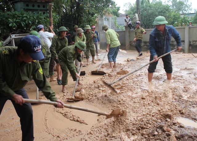 Công an xã Hưng Yên Nam giúp người dân thu dọn số bùn đất tràn vào trong sân.