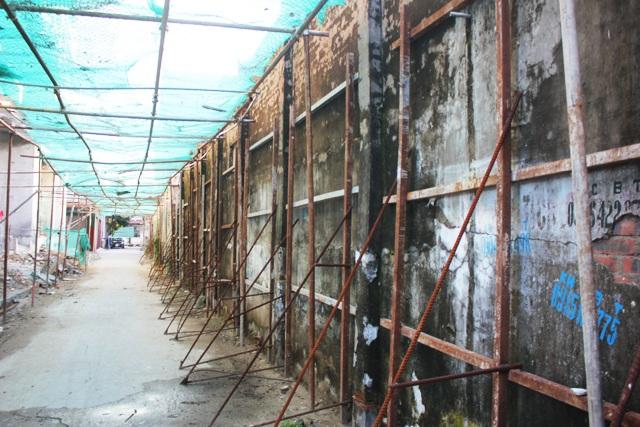 Các bức tường công trình nhà dân tiếp giáp với khu vực xây dựng được chống đỡ bằng hệ thống cọc sắt.
