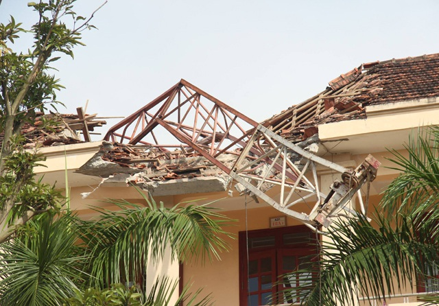 Chiếc cần cẩu bị gãy nằm vắt qua mái nhà dãy phòng học 3 tầng của Trường THPT Lê Viết Thuật.